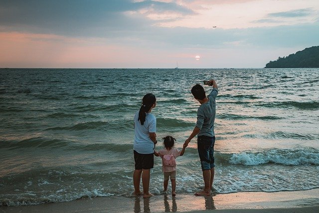 A family of three taking a selfie at the beach
