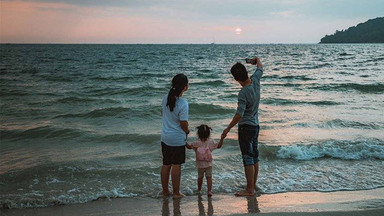 A-family-of-three-taking-a-selfie-at-the-beach